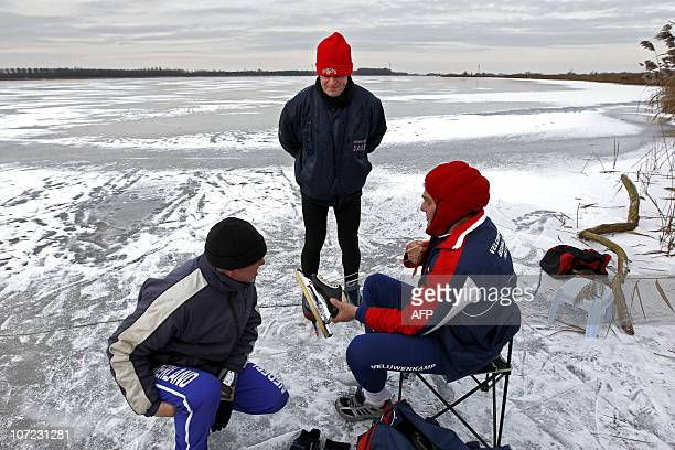 Ice skaters put on their skates on the frozen Veluwe lake near Elburg in eastern Netherlands on December 1 2010 Winter weather brought temperatures...