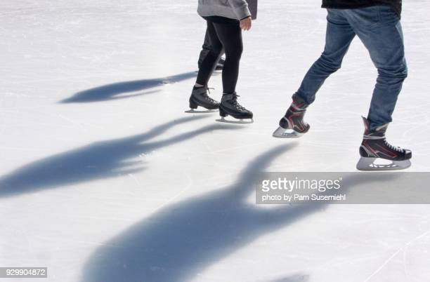 ice skaters' shadows on outdoor rink - ice rink stock photos and pictures