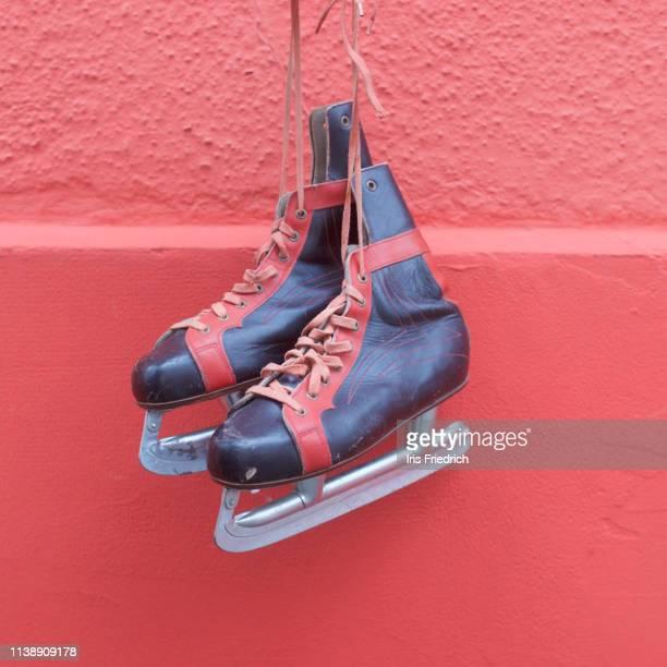 ice skates hanging against red wall - schlittschuh stock-fotos und bilder