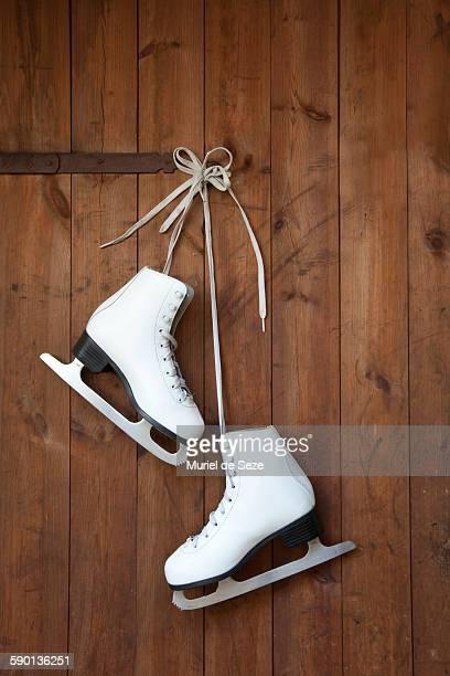 ice skates hanging from wooden door - schlittschuh stock-fotos und bilder