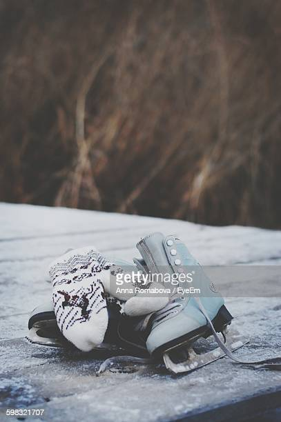 Ice Skates With Gloves On Snow Covered Field