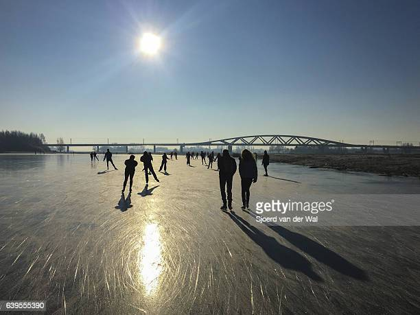 ice skating on a frozen lake in holland during winter - zwolle stock photos and pictures