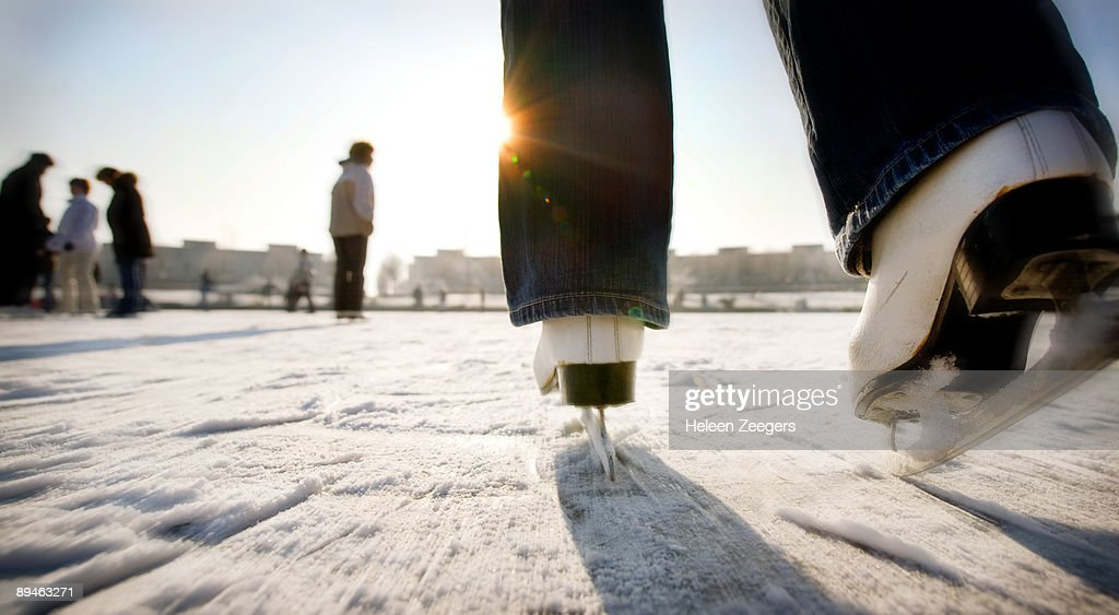 Ice skating with speed towards sun in Holland : Stock Photo