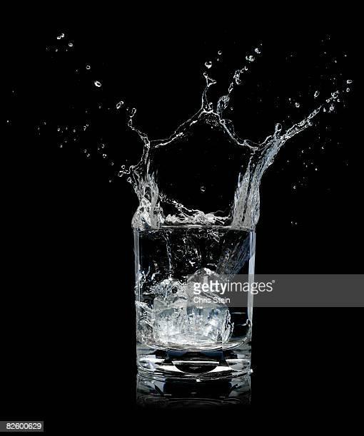 Ice splashing into water glass