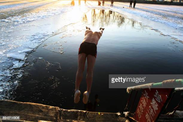 A ice swimmer dives into a partly frozen lake in Shenyang in China's northeastern Liaoning province on December 18 2017 Winter swimming is believed...