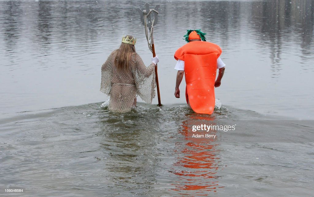 Ice swimming enthusiasts dressed as Neptune (L) and a carrot enter the cold waters of Orankesee lake during the 'Winter Swimming in Berlin' event on January 12, 2013 in Berlin, Germany. A local swimmers' group called the 'Berlin Seals' invite ice swimmers from across Germany and abroad to the annual event, which, despite warmer temperatures this winter and a lack of ice, was still held. Members claim ice swimming is good for the body's blood circulation.
