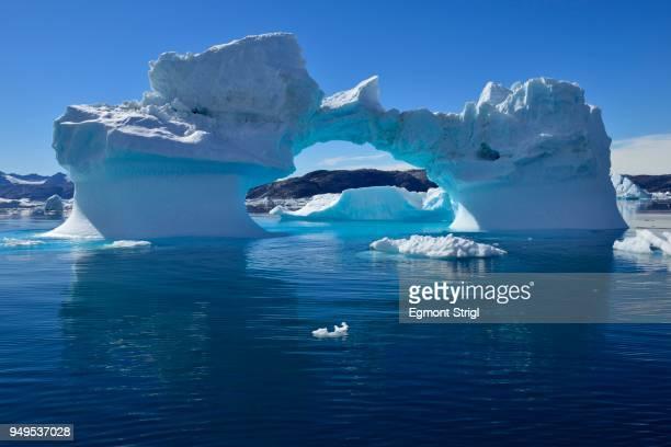 iceberg drifting in sermilik fjord, east greenland, greenland - natuurlijke brug stockfoto's en -beelden