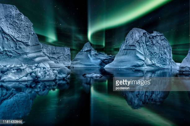 iceberg floating in greenland fjord at night with green northern lights - greenland stock pictures, royalty-free photos & images