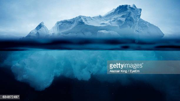 iceberg floating on sea against sky - berg stock pictures, royalty-free photos & images