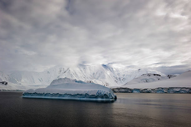 Iceberg In The Ocean And Snow Covered Mountains Along The Coastline
