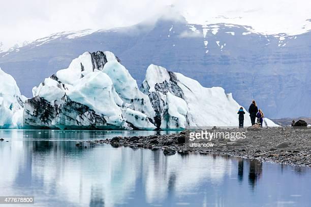 Iceberg, Jökulsárlón Lagoon, family stand on the shore, Iceland