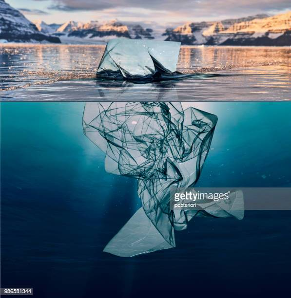 iceberg of garbage plastic floating in ocean with greenland back - inquinamento foto e immagini stock