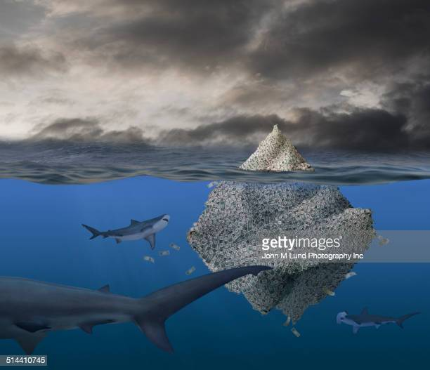 Iceberg of money floating with sharks in stormy ocean