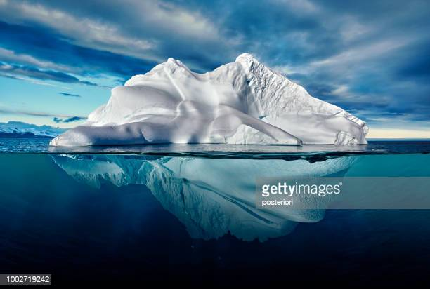 iceberg with above and underwater view taken in greenland. - sopra foto e immagini stock