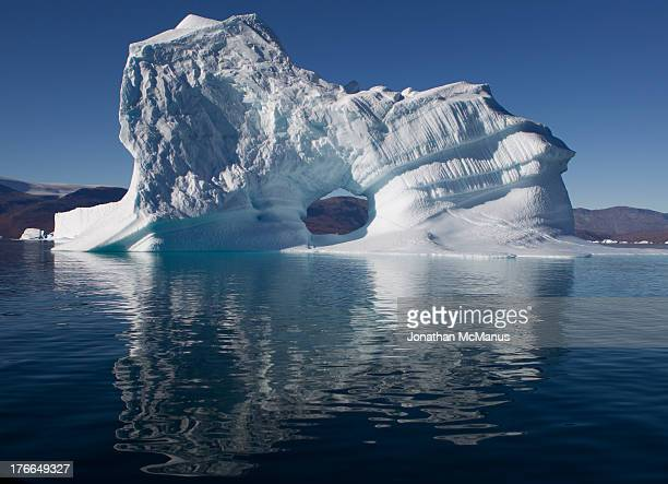 Iceberg with diffused reflection in bright sunshine near King Oscar Fjord in North East Greenland. The iceberg has a hole in its centre and linear...