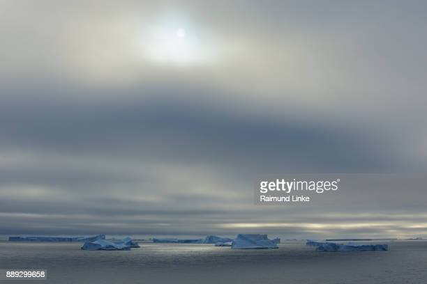 Iceberg with low-hanging clouds and sun, Antarctic Sound, Antarctic Peninsula, Antarctica