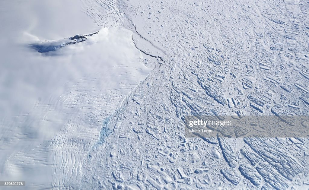Icebergs and sea ice (R) float next to land ice (L), as seen from NASA's Operation IceBridge research aircraft, near the coast of the Antarctic Peninsula region, on November 3, 2017, above Antarctica. NASA's Operation IceBridge has been studying how polar ice has evolved over the past nine years and is currently flying a set of nine-hour research flights over West Antarctica to monitor ice loss aboard a retrofitted 1966 Lockheed P-3 aircraft. According to NASA, the current mission targets 'sea ice in the Bellingshausen and Weddell seas and glaciers in the Antarctic Peninsula and along the English and Bryan Coasts.' Researchers have used the IceBridge data to observe that the West Antarctic Ice Sheet may be in a state of irreversible decline directly contributing to rising sea levels. The National Climate Assessment, a study produced every 4 years by scientists from 13 federal agencies of the U.S. government, released a stark report November 2 stating that global temperature rise over the past 115 years has been primarily caused by 'human activities, especially emissions of greenhouse gases'.