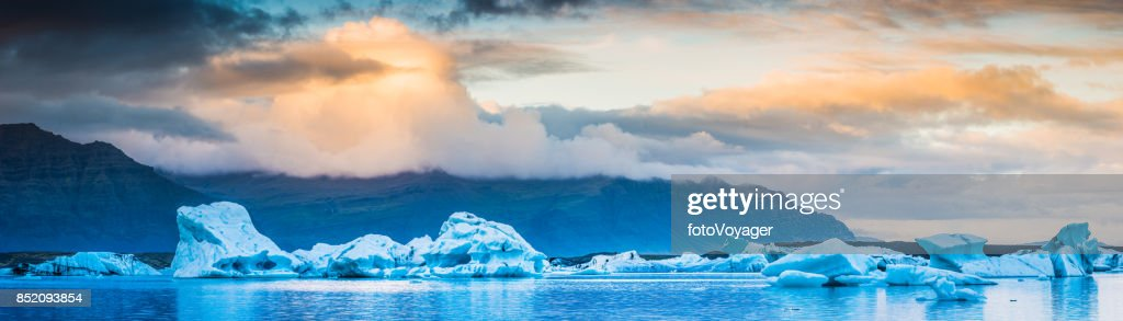 Icebergs and sunset cloudscape panorama tranquil Artctic Ocean shore Iceland : Stock Photo
