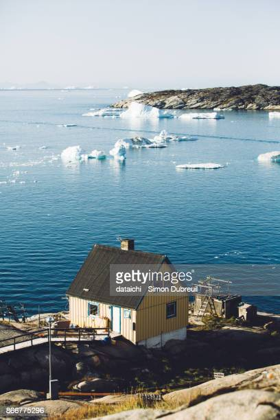 Icebergs and wooden house in Ilulissat, Disko Bay