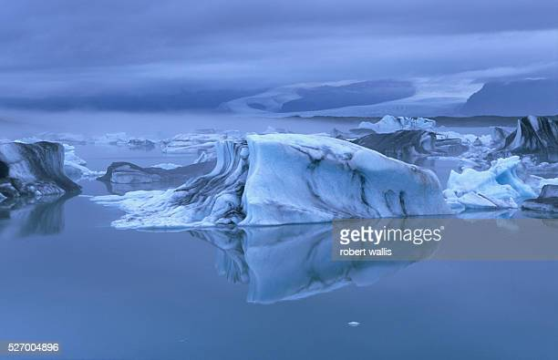 Icebergs calve from Vatnajokull glacier on its south side at Jokulsarlon where it meets the sea. The glacier is visible in the background. |...