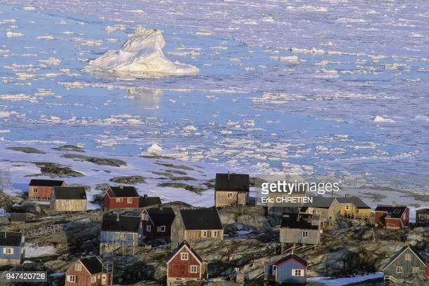 Icebergs et ''iceblocs'' derivants sur le fjord Sermilk devant les maisons traditionnelles du petit village inuit de Tiniteqilaaq Region d'Ammassalik