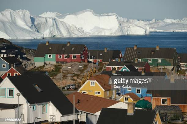 Icebergs floating at the mouth of the Ilulissat Icefjord loom behind the town center on July 30, 2019 in Ilulissat, Greenland. As the Earth's climate...