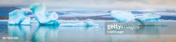 Icebergs floating in Arctic ocean lagoon below glaciers panorama Iceland