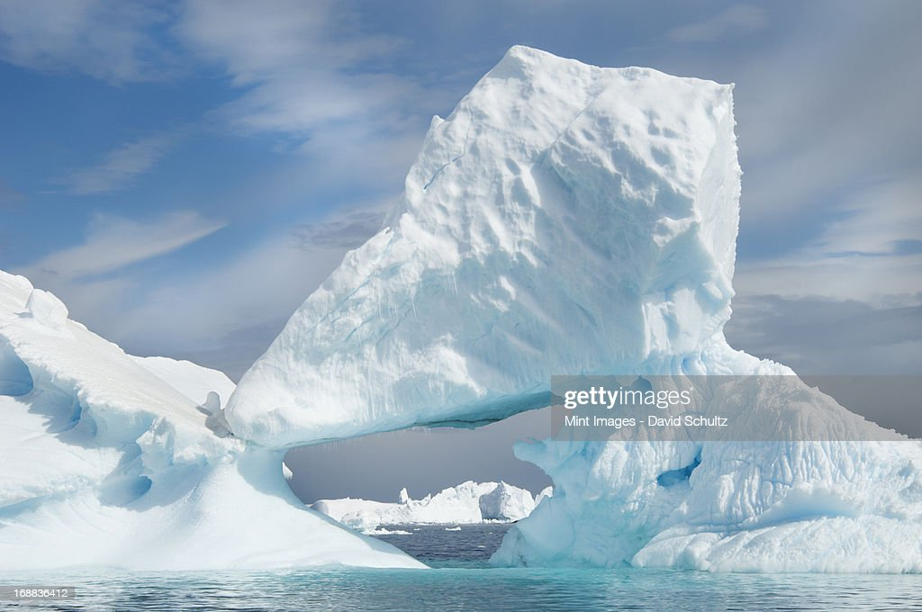 Icebergs floating on the Antarctic southern oceans. Eroded by wind and weather, creating natural ice arches. : Stock Photo