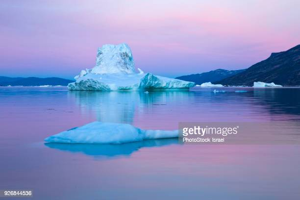 Icebergs in calm water during midnight sun, Jakobshavn, Vestgronland, Greenland