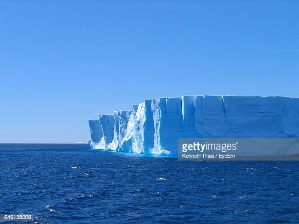 Icebergs In Sea Against Clear Blue Sky