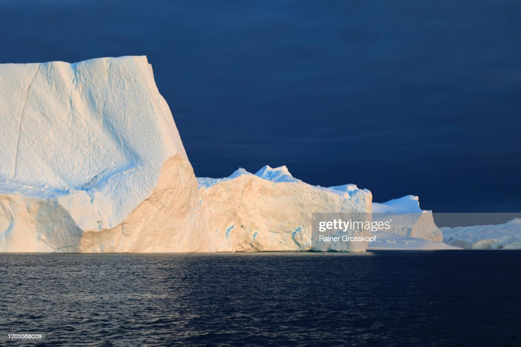 Icebergs in the Icefjord in the warm light of the midnight sun : Stock-Foto