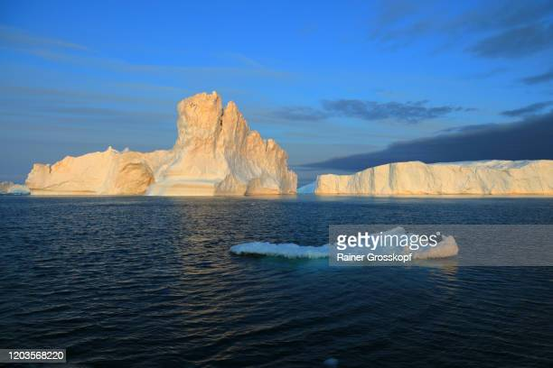 icebergs in the icefjord in the warm light of the midnight sun - rainer grosskopf stock-fotos und bilder