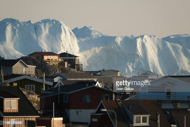 Icebergs in the Ilulissat Icefjord loom behind buildings on August 04, 2019 in Ilulissat, Greenland. The Sahara heat wave that recently sent...