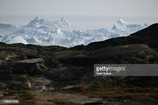 Icebergs loom from the Ilulissat Icefjord during a week of unseasonably warm weather on August 3 2019 near Ilulissat Greenland The Sahara heat wave...
