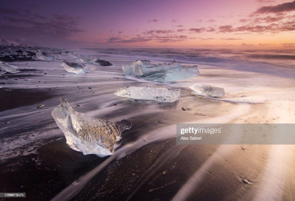 Icebergs on a beach at sunrise. : Stock Photo
