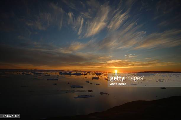Icebergs that broke off from the Jakobshavn Glacier are seen floating in the water as the sun reaches its lowest point of the day on July 23, 2013 in...