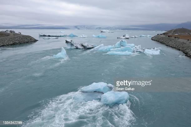 Icebergs that have broken off of receding Breidamerkurjokull glacier, which is seen behind, clog a river leading from Jokulsarlon lake to the ocean...