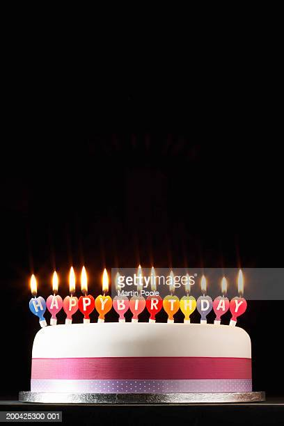 iced cake lit with happy birthday candles - birthday cake stock photos and pictures
