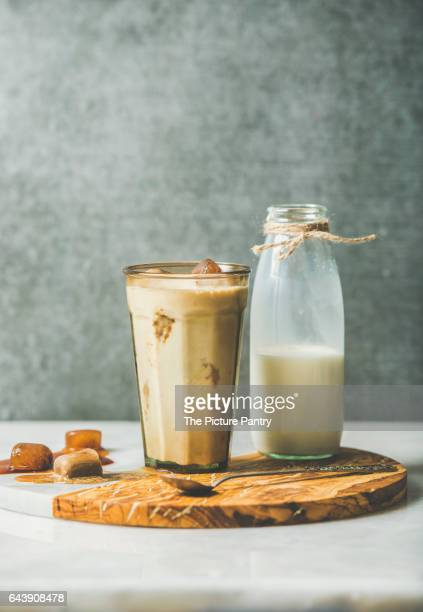 Iced caramel latte summer coffee cocktail with milk and frozen coffee ice cubes in glass on serving olive wood and marble board over grey table, dark plywood wall