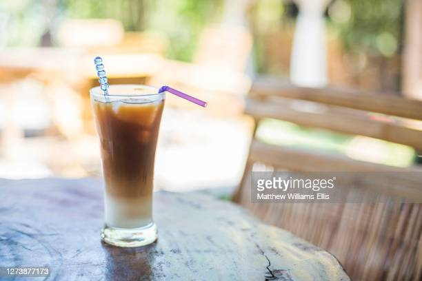 iced coffee drink with plastic straw and plastic stirrer, contributing to overuse of single use plastic contributing to global warming and climate emergency - coffee drink stock pictures, royalty-free photos & images