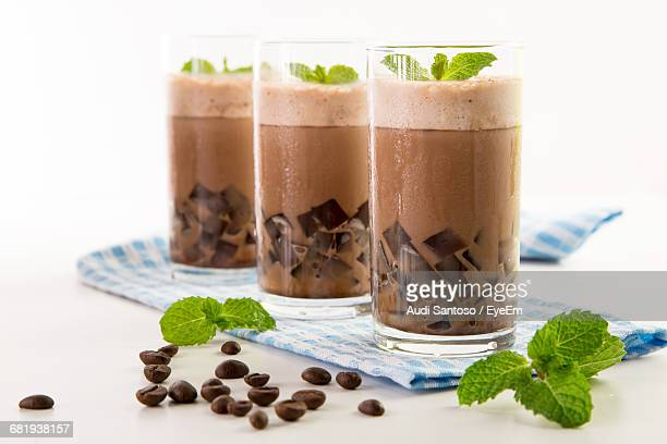 Iced Coffee In Glasses By Coffee Beans And Mint Leaves On Table