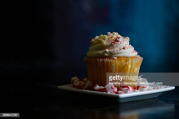 iced cupcake on dark background - nanette j stevenson stock photos and pictures