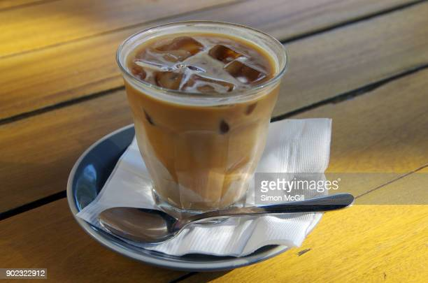 iced latte in a glass on a wooden outdoor cafe table - paper napkin stock photos and pictures
