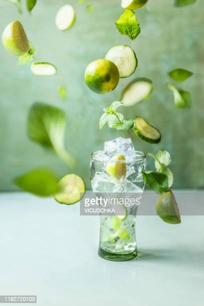 iced summer drink in glass with flying green ingredients - ミント ストックフォトと画像