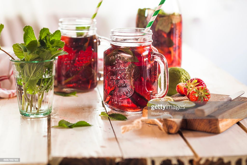 Iced tea with fruits, hibiscus, strawberries, mint, limes : Stock Photo