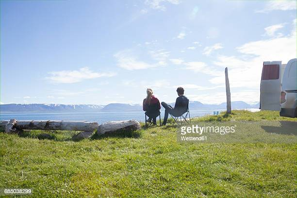 Iceland, back view of couple sitting on camping chairs looking at view