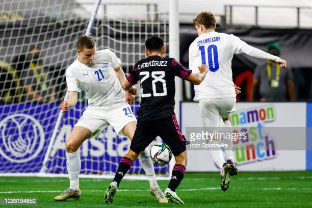 Iceland Brynjar Ingi Bjarnason , Iceland Isak Bergmann Johannesson and Mexico Carlos Rodriguez chase the ball during the game between Mexico and...