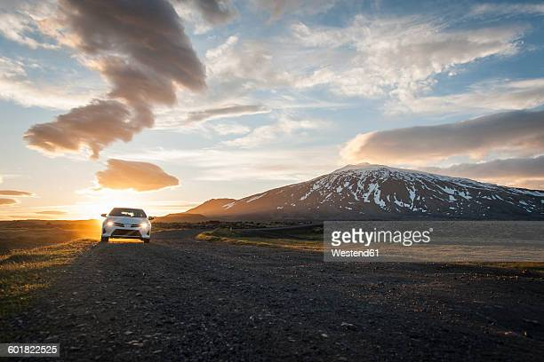 Iceland, car on gravel road under midnight sun