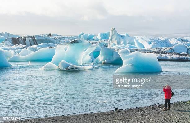 Iceland Jokulsarlon glaciers and icebergs on lake lagoon with photographers on edge of Vatnajokull National Park in Southeast Iceland.