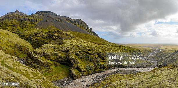 Iceland landscape with a river, grass and moss covered rocks